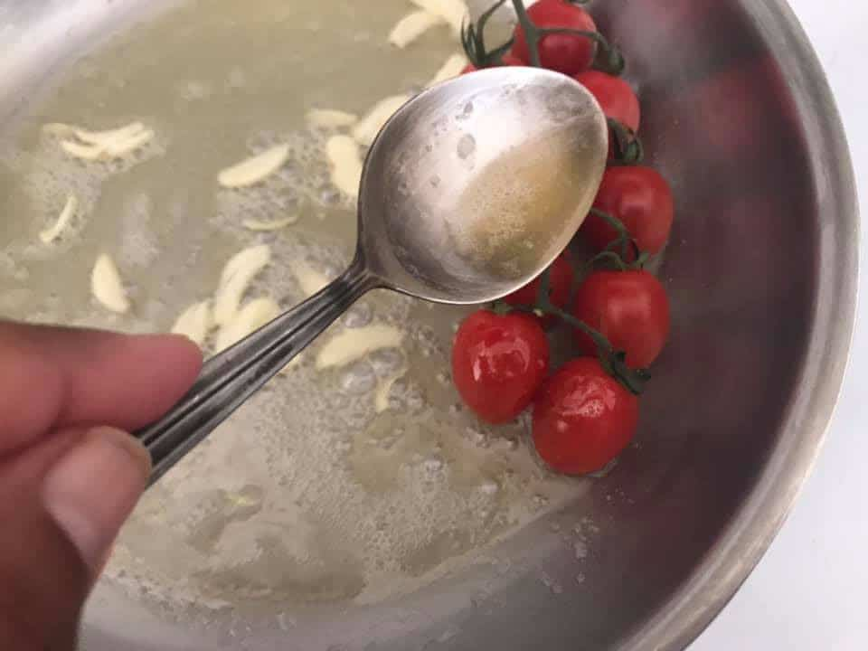 butter being poured on cherry tomatoes