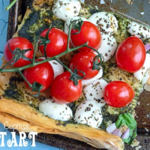 top view of cherry tomatoes on the vine on a phyllo dough tart with melted mozzarella balls