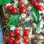 Top view of caprese tart with tomatoes on the vine, mozzarella balls and basil leaves