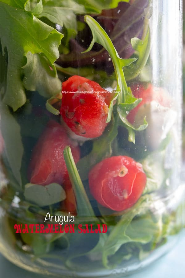 Closeup view of a mason jar filled with arugula and watermelon balls and mozzarella balls