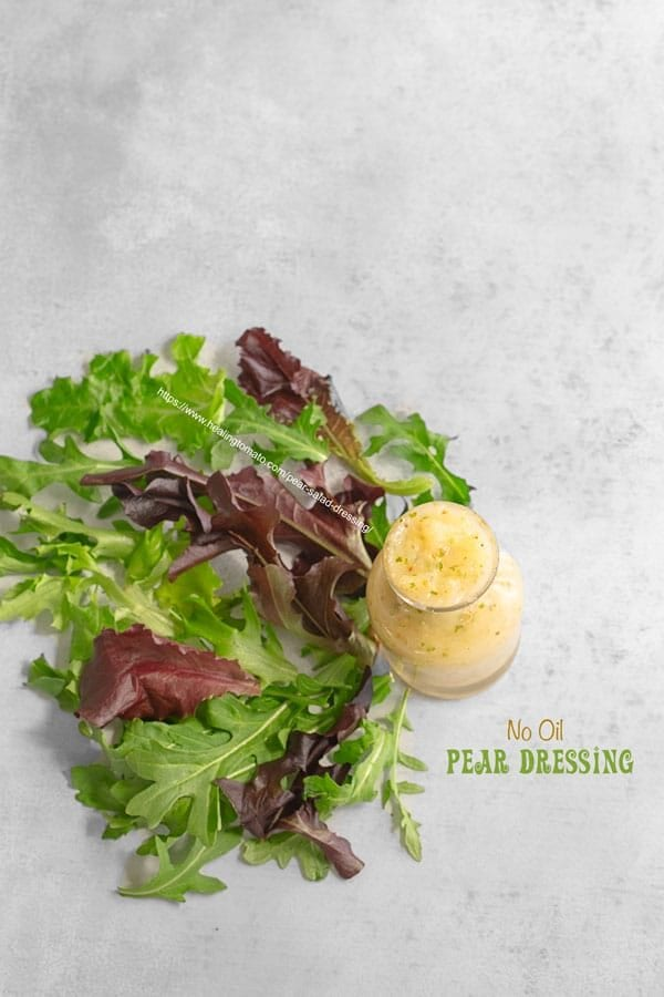Top view of a small glass bottle filled with pear salad dressing and arugula shaped as a fan next to it