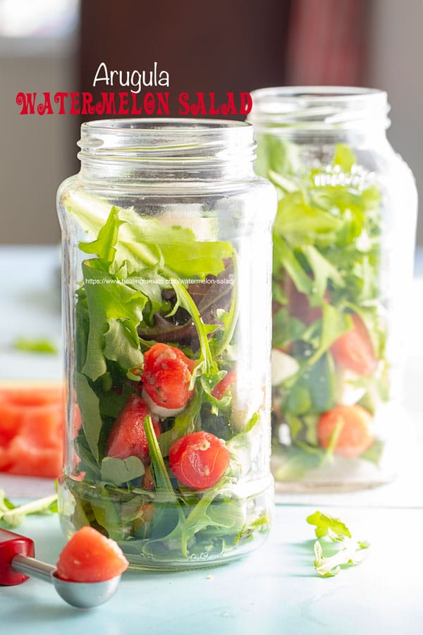 Front view of 2 mason jars filled with arugula and watermelon balls and mozzarella balls