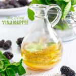 Front view of a small glass cruet filled with mint vinaigrette. Background has mint and blackberry