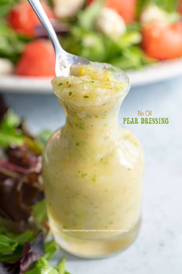 Front view of a small glass bottle filled with pear dressing with arugula salad in the background