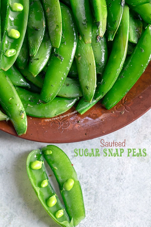 Top view of a brown plate filled with cooked sugar snap peas with 2 open pea pods