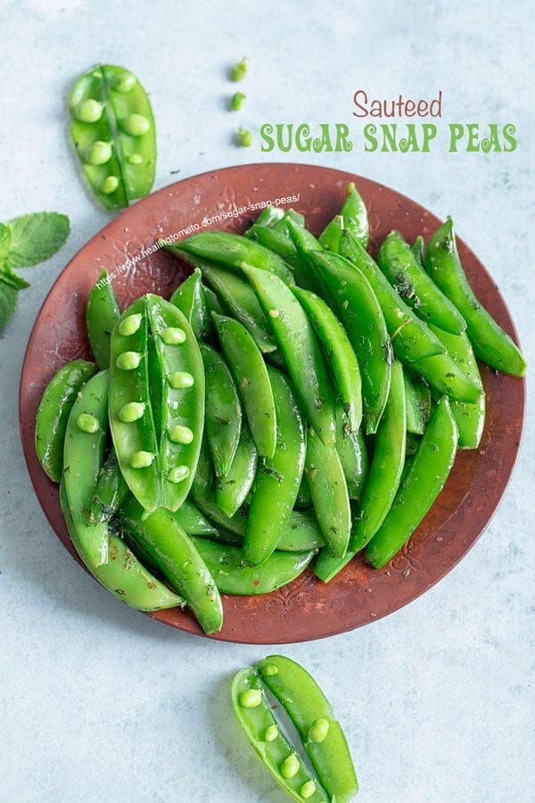 Top view of a brown plate filled with cooked sugar snap peas with 3 open pea pods open and a few peas on the side