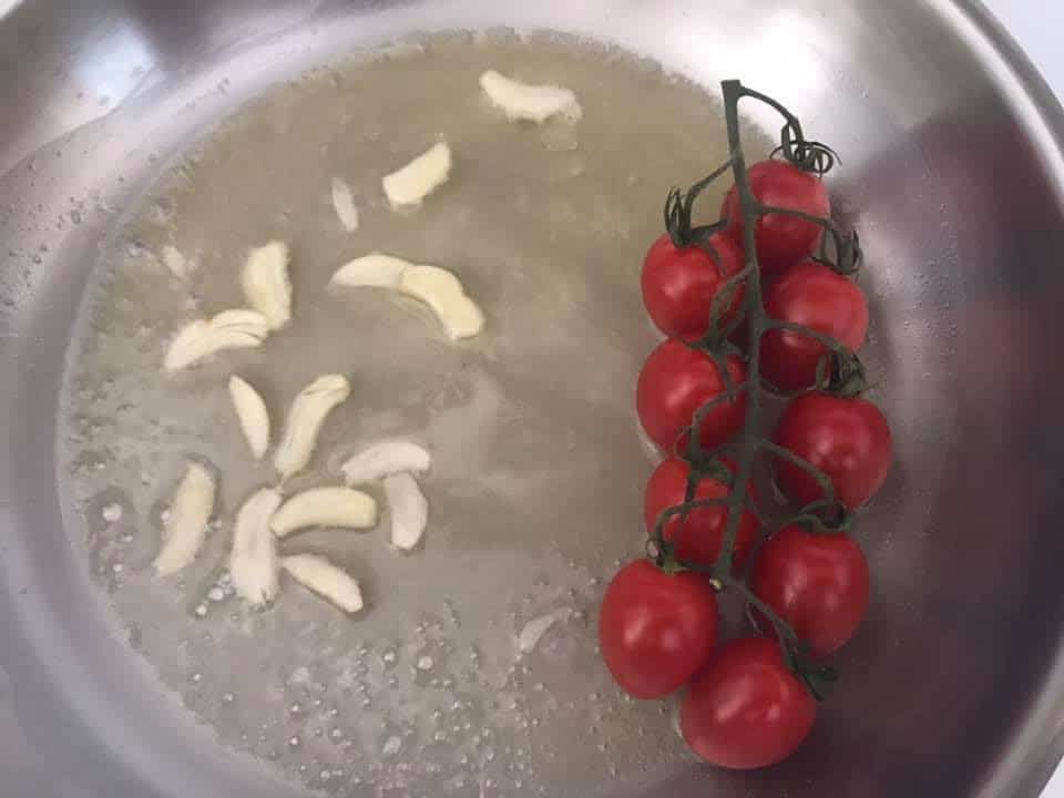 1 branch of cherry tomatoes added to a pan with butter and garlic