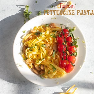top view of tuscan fettuccine pasta with cherry tomatoes and basil for garnish