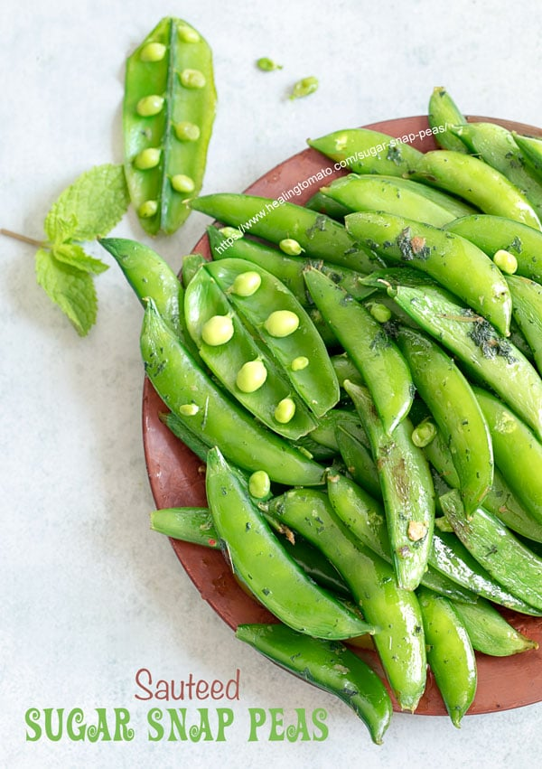 Overhead view of part of a brown plate filled with cooked sugar snap peas with 2 open pea pods open