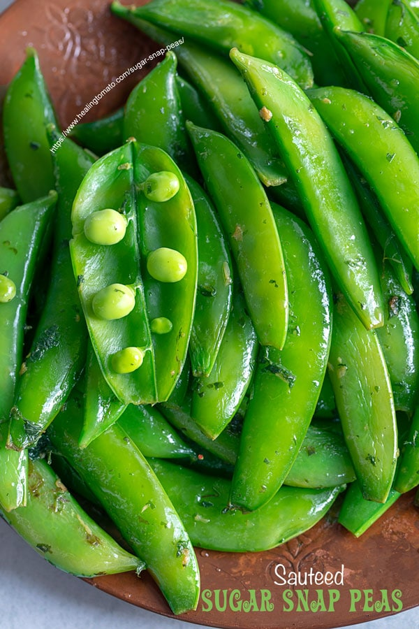 Top view of an open sugar snap pea pod with peas showing