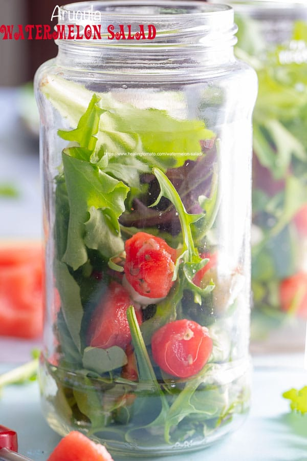 Front view of a mason jar filled with arugula and watermelon balls and mozzarella balls