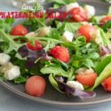 Front view of a grey plate with arugula, melon balls and mozzarella balls