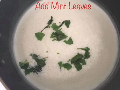 Top view of mint added to hot milk