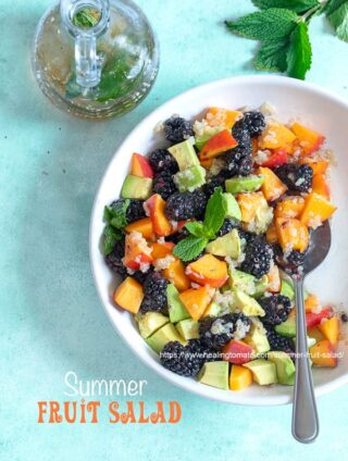 Top view of a white bowl with blackberries, peaches, avodado and quino