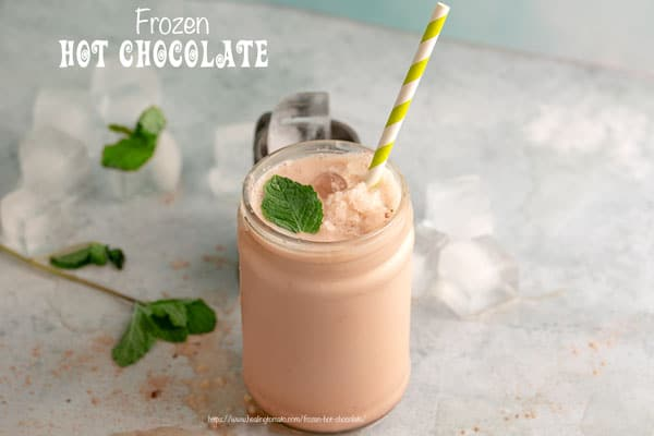 Front View of Frozen Chocolate Drink in a tall glass bottle with mint on the side