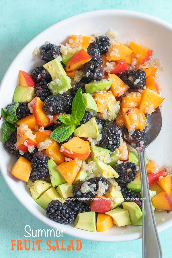 Closeup view of a white bowl with blackberries, peaches, avodado and quino