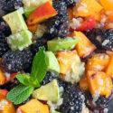 closeup view of quinoa fruit salad with a mint leaf garnish
