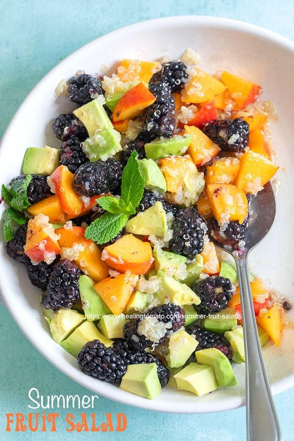 Closeup view of a white bowl with blackberries, peaches, avodado and quino