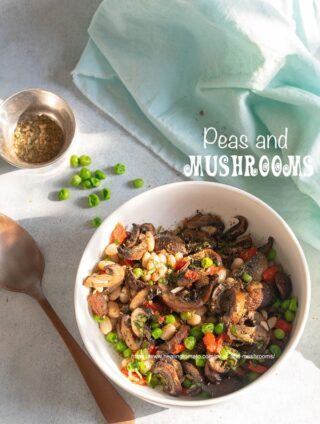 Top view of a white bowl filled with mushrooms, peas, navy beans and bell peppers