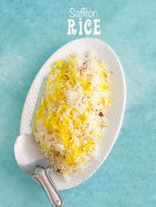 Top view of a white oval plate with saffron rice and a stainless steel rice server on the side