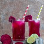 Front view of two small glasses filled with beet lemonade. Ice cubes inside, red, green paper straw to the side and a slice of beet lemonade for garnish