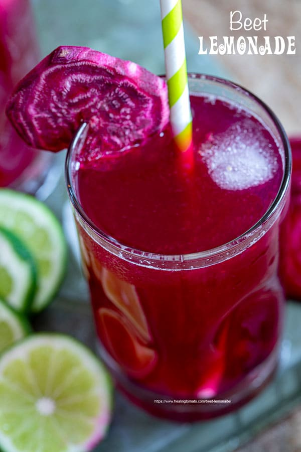 Closeup view of 1 small glasses filled with beet lemonade. Ice cubes inside, a green paper straw to the side and a slice of beet lemonade for garnish