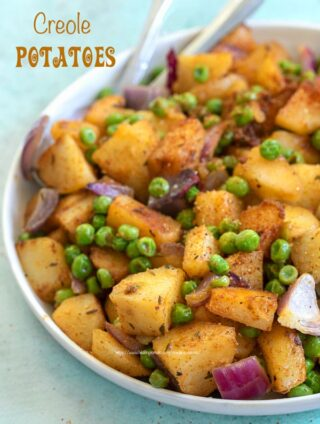 Angle and closeup view of potatoes and peas on a white plate