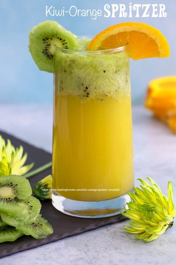 Front view of a glass filled with orange spritzer an topped with muddled kiwi