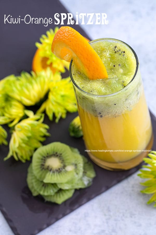 Top view of a glass filled with orange spritzer an topped with muddled kiwi