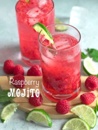 Front view of a glass filled with raspberry mojito recipe and surrounded by raspberries and lime
