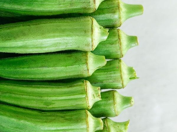 Top view of 2 rows of okra lined up on the left side of the screen - how to cook okra