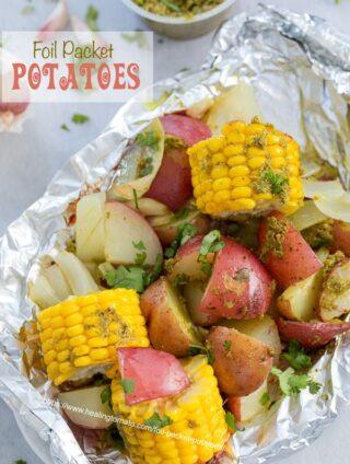 Top view of potatoes and mini corn on the cob inside an aluminium wrap