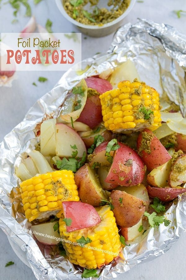 Top view of potatoes and mini corn on the cob inside an aluminium wrap