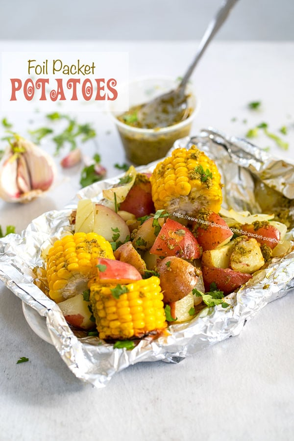 Angle view of potatoes and mini corn on the cob inside an aluminium wrap