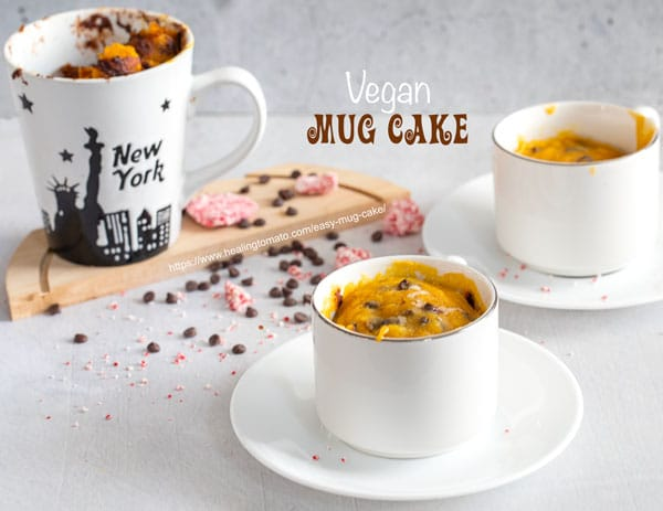 front view of 3 a mug filled with an easy mug cake. Two more mugs in the background and chocolate chips strewn around the mugs