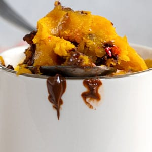 closeup view of a spoon filled with pumpkin and chocolate placed on the rim of a mug