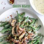 Top view of green beans and mushrooms in a white plate with red pepper flakes for garnish