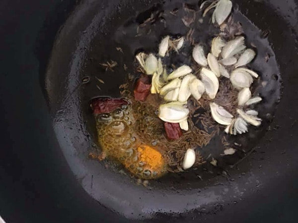 top view of garlic, turmeric, dry chili in oil in a frying pan