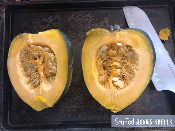 Acorn squash cut into half and placed on a baking tray with a long knife on the side