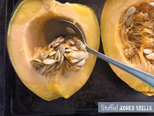 A stainless steel spoon beginning to scoop out the insides of a halved acorn squash