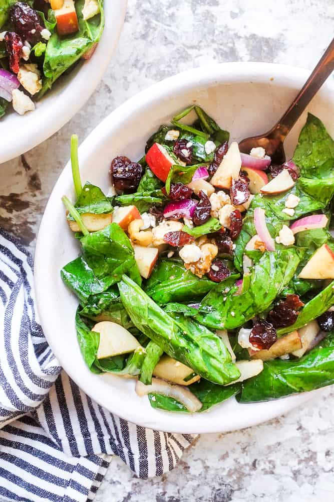 Top view of spinach salad in a white bowl - Erhardtseat - dried cranberries