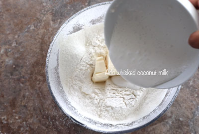 whisked coconut milk being poured into the flour and vegan butter bowl