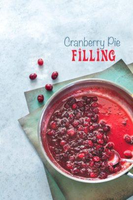 Top view of a stainless steel pan filled with cranberry pie filling on a blue background with a few cranberries on the side