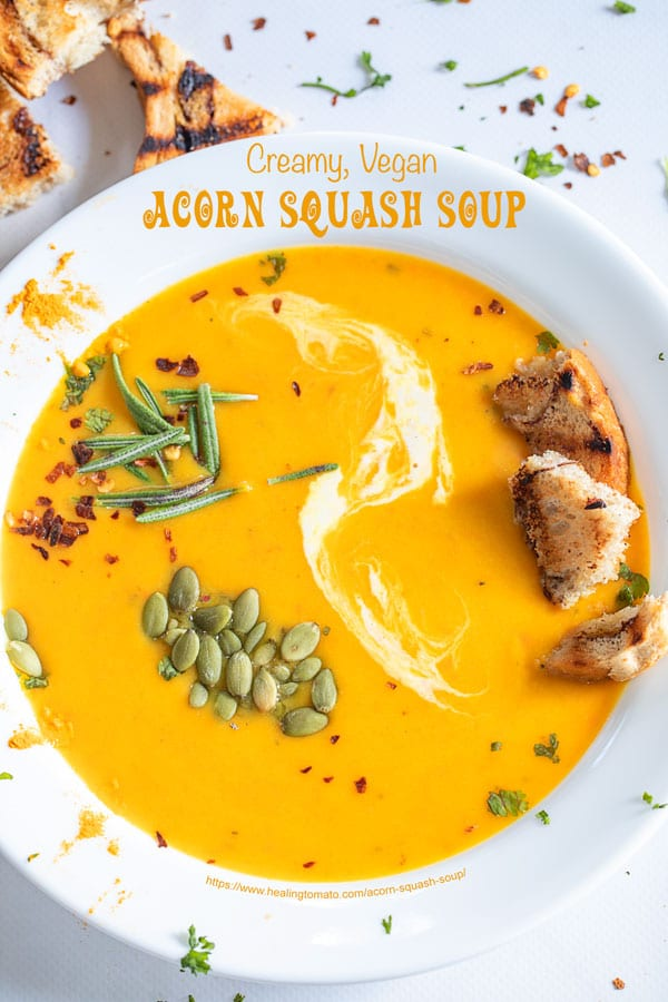 Closeup view of a white plate filled with acorn squash soup with garnish and grilled croutons