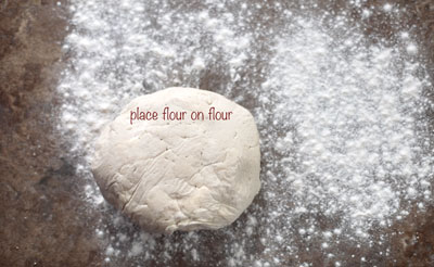 A ball of pie crust dough on a floured surface