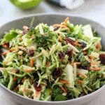 Angle view of a grey bowl with broccoli and apple slaw