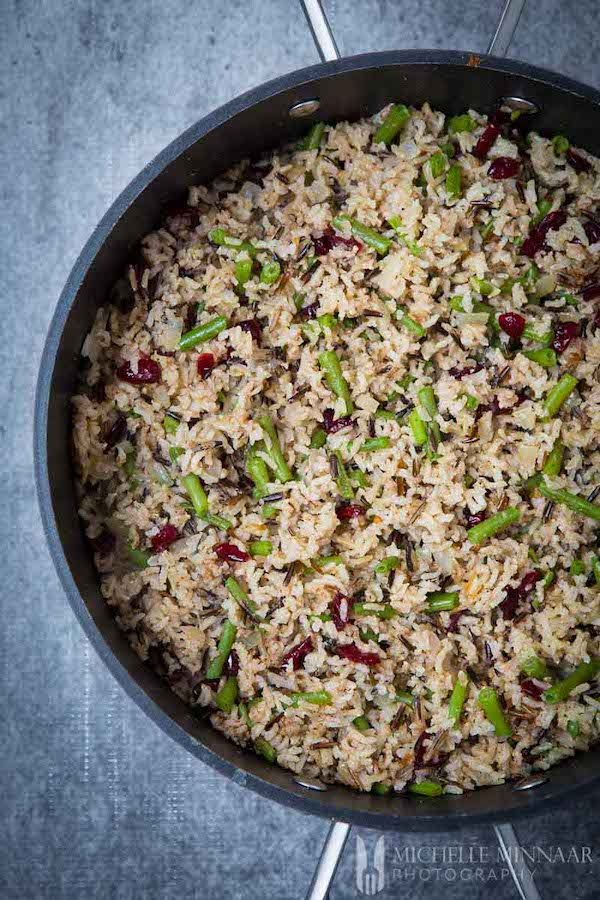 Top view of a black pan filled with christmas rice - dried cranberries