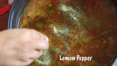 The author drizzling lemon pepper over the vegan sausage stew