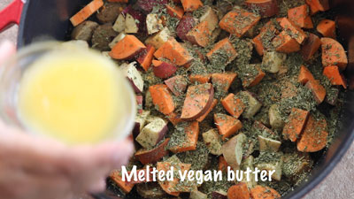 Melted vegan butter being drizzled over the ingredients in the dutch oven