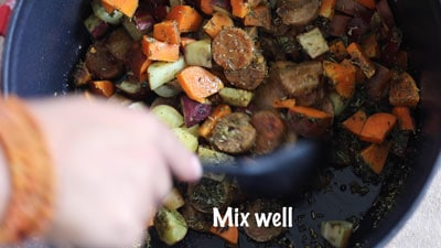 The author mixing the contents of the dutch oven using a black plastic spoon